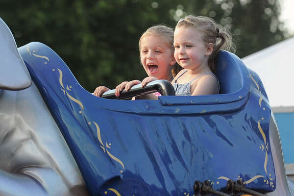 Greenwich kids, Vivian Partridge, 4, left, and Ava Kiraly, also 4, enjoy the flying elephant ride during the annual St. Catherine of Siena Church Carnival of Fun at the church in the Riverside section of Greenwich, Conn., Wednesday, July 13, 2016. The remaining nights for the Carnival of Fun are Thursday - Saturday, 6 p.m. - 11 p.m., at the church located at 4 Riverside Avenue in Greenwich. First prize in the Carnival of Fun raffle ($25 per ticket) is a red metallic 2016 BMW 228i.