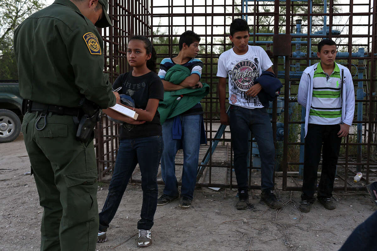 Central American immigrants including a girl who said she came alone from Honduras, left, are questioned by a U.S. Border Patrol agent after they crossed the Rio Grande River by boat into the United States on Wednesday, August 13, 2014.