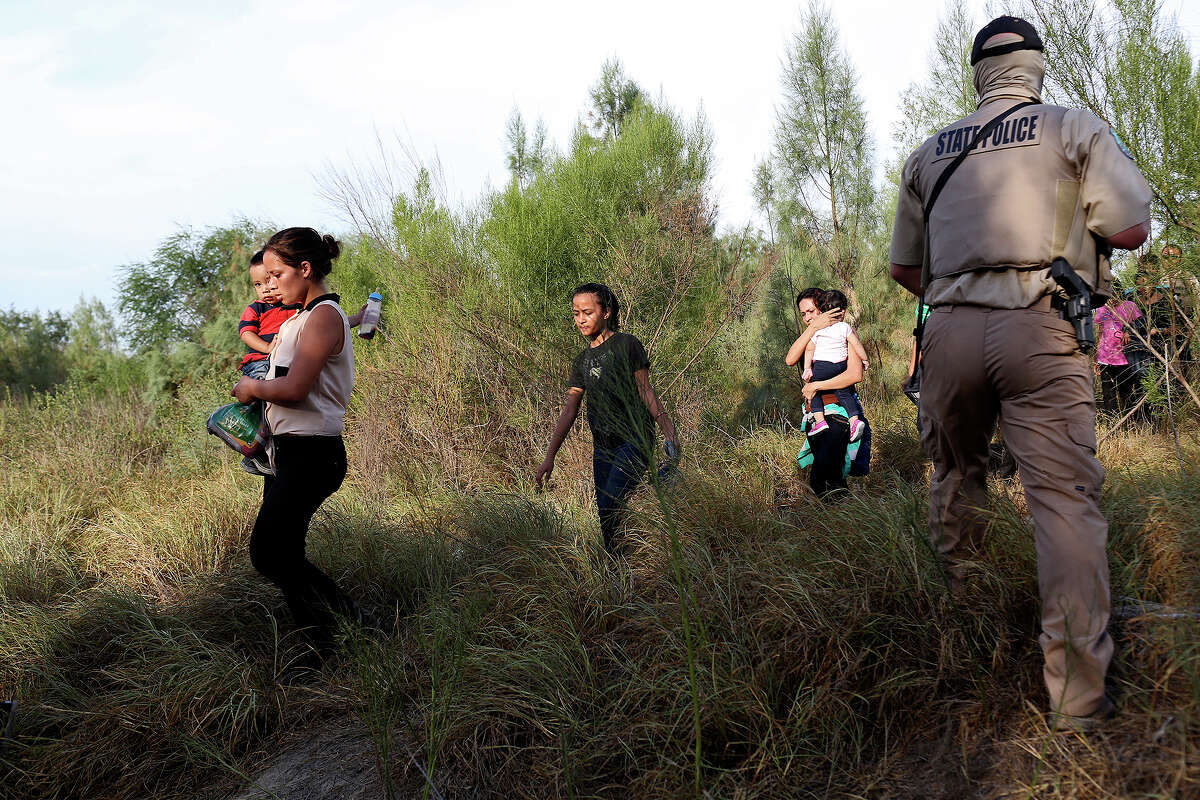 Central American immigrants including Maria Bertalina Ramirez, 21, left, of Honduras, with her son, Jose Joel, 1, are guided by Texas Game Wardens and a U.S. Border Patrol agent after they crossed the Rio Grande River by boat into the United States on Wednesday, August 13, 2014. The group of 14 was questioned and taken in vans to be processed.