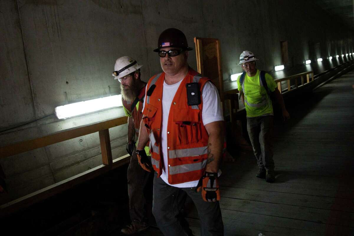 Construction workers leave the tunnel from the south entrance.