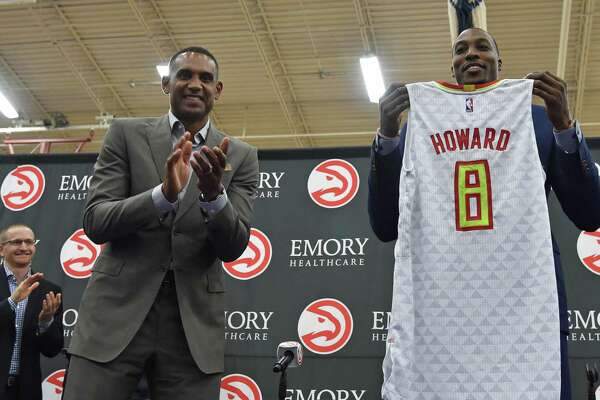 Dwight Howard holds the jersey presented to him by Grant Hill, left, during a news conference introducing Howard as the newest member of the Atlanta Hawks Wednesday July 13, 2016, in Atlanta.  (Brandt Sanderlin/Atlanta Journal-Constitution via AP)