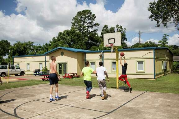 Residents of the Tejano Center for Community Concerns Emergency Shelter play basketball outside the facility on Tuesday, July 12, 2016, in Houston. The emergency shelter stands at the site that city council is considering allocating $3.5 million in federal grants to help build an affordable housing complex geared toward youth aging out of foster care. ( Brett Coomer / Houston Chronicle )