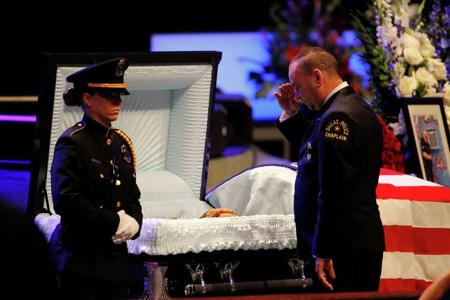 A Dallas Police Department chaplain salutes beside the casket of Senior Corporal Lorne Ahrens, one of five officers killed in last week's sniper attack, during his funeral at Prestonwood Baptist Church in Plano, Texas, on Wednesday, July 13, 2016. (Paul Moseley/Fort Worth Star-Telegram/TNS) Photo: Paul Moseley, MBR / TNS / Fort Worth Star-Telegram