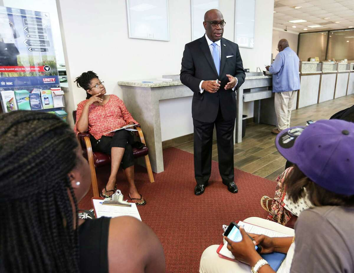 Unity National Bank president John Scroggins talks to people opening up a new account at the bank as they wait in line on Wednesday, July 13, 2016, in Houston. ( Elizabeth Conley / Houston Chronicle )