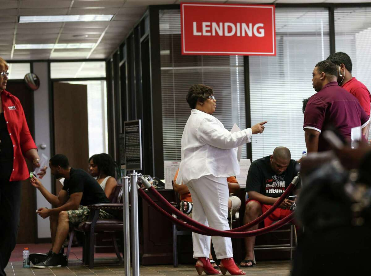 Ingrim Mitchem, account analysis for Unity National Bank, directs people looking to open a new account in the lobby on Wednesday, July 13, 2016, in Houston. ( Elizabeth Conley / Houston Chronicle )