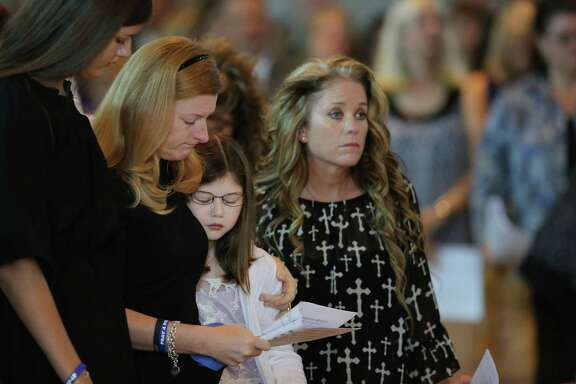 Heidi Smith (second to left) stands between her daughters, Victoria (left) and Caroline Smith (center), with Dallas Sr. Cpl. Marcie St. John (right) during the funeral for her husband, Dallas police sergeant Michael Smith.