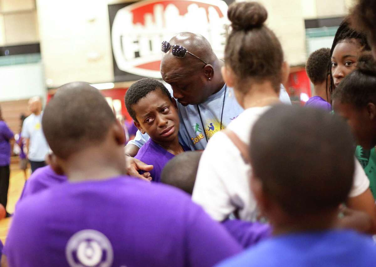 Joseph Sanders is comforted by his coach after his team loss in the 21st Annual Harris County Street Olympics' 3-on-3 Basketball Championship Tournament on Wednesday, July 13, 2016, in Houston.