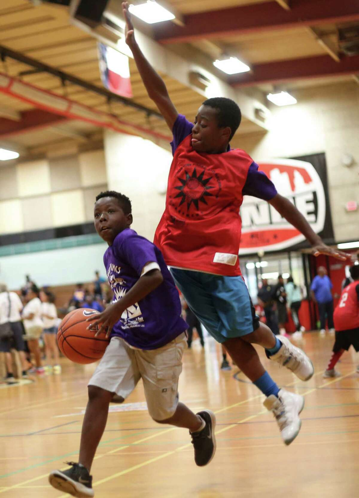 Benson Dorsey drives around Joseph Sanders during the 21st Annual Harris County Street Olympics' 3-on-3 Basketball Championship Tournament on Wednesday, July 13, 2016, in Houston.