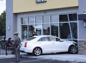 A car crashed through the front window at the Starbuck's on Clifton Country Road in Clifton Park  Thursday morning but no one was hurt. The incident happened shortly after 6 a.m. A Cadillac sedan crash into the window at the 22 Clifton Country Road home. (Skip Dickstein / Times Union)