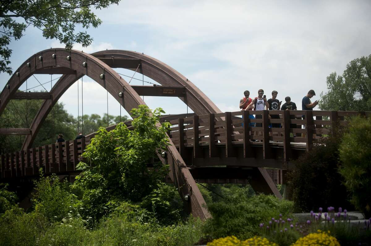 People use their smart phones to search for Pokemon on the Tridge while playing the new game, Pokemon Go, on Tuesday afternoon. Pokemon Go uses smart phone's GPS and clock to detect where and when players are in the game and make Pokemon