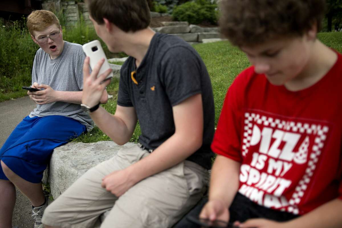 Midland residents from left: Bradan Bukaweski, 16, reacts as Nick Kerkau, 16, shows him a Pokemon he caught while Hunter Stilwell, 16, searches for other Pokemon near the boat launch on Wednesday afternoon.