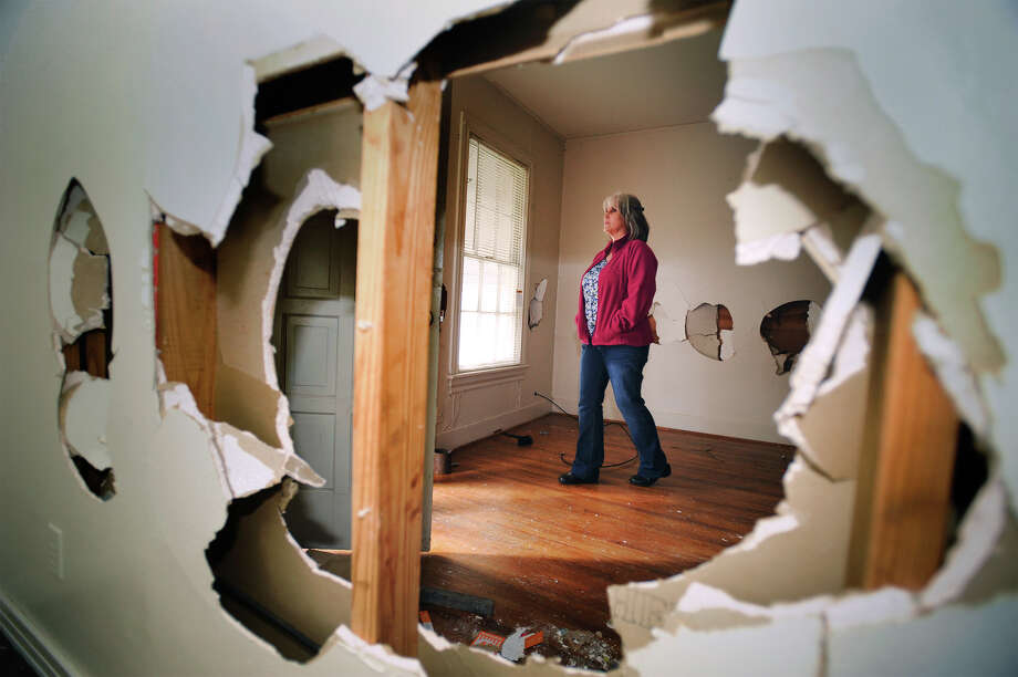 Elaine Leger walks Tuesday through Stanley Leger's rent home that was heavily damaged while former tenants resided there. A June altercation between Leger and the tenants, including a .22 caliber round fired by Leger, lead to Leger's shooting death by a Beaumont Police officer. 