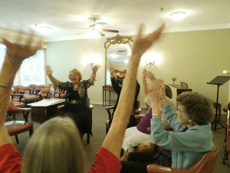 Janet Carroll, the Laughter Yoga nurse, leads the Treemont Retirement Community group in an exercise. Photo: Courtesy Of Treemont