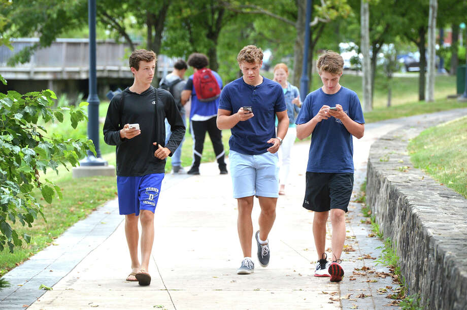Tighe Ekern, 16, John Byrne, 17, and Reese Gregory, 16 all from Darien, play Pokemon Go while walking along North Water St. on Monday July 11 2016, in Norwalk Conn. Photo: Alex Von Kleydorff / Hearst Connecticut Media / Connecticut Post
