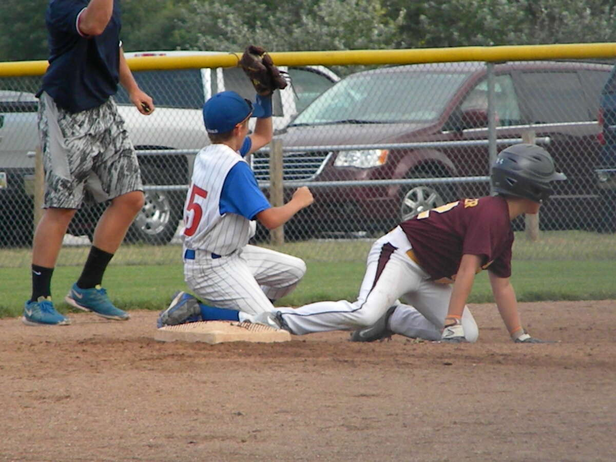 Midland Northeast's Ethan Gould shows the ball to the umpire after tagging out an Union Township baserunner.