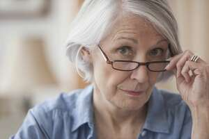 Senior Caucasian woman peering over her eyeglasses