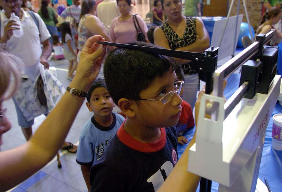 Javier Delgado of Killeen, Texas, has his height and weight checked as his brother, Jose, in blue shirt, looks on during an Hispanic Health Fair in Killeen, Texas, Sunday, June 5, 2005. The event was sponsored by local health clinics to assist Hispanics in the area with health screenings. (AP Photo/Killeen Daily Herald, Steve Traynor) Photo: STEVE TRAYNOR, MBR / KILLEEN DAILY HERALD