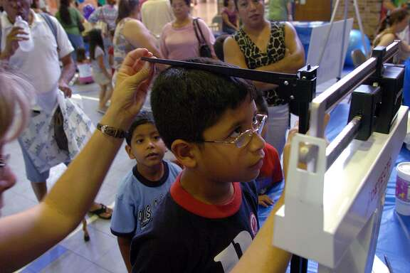 Javier Delgado of Killeen, Texas, has his height and weight checked as his brother, Jose, in blue shirt, looks on during an Hispanic Health Fair in Killeen, Texas, Sunday, June 5, 2005. The event was sponsored by local health clinics to assist Hispanics in the area with health screenings. (AP Photo/Killeen Daily Herald, Steve Traynor)