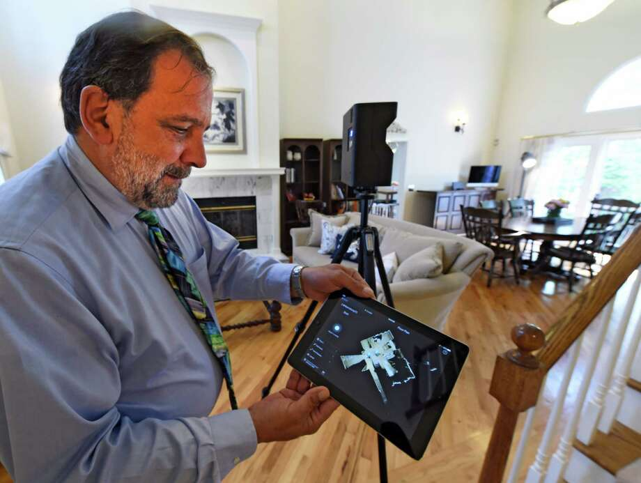 Miguel Berger, president of Better Homes and Gardens Real Estate Tech Valley demonstrates the new 3D camera used for real estate applications June 2, 2016 at a home in Rexford, N.Y. (Skip Dickstein/Times Union) Photo: SKIP DICKSTEIN / 40036826A