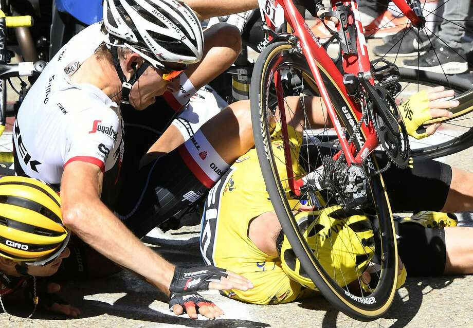 "Britain's Chris Froome, wearing the overall leader's yellow jersey, right, Netherlands� Bauke Mollema, center, and  Australia�s Richie Porte crash at the end of the twelfth stage of the Tour de France cycling race with start in Montpellier and finish six kilometers (3.7 miles) before the Mont Ventoux, France, Thursday, July 14, 2016. The wind, combined with a temperature just above the freezing level on top of the ""Giant of Provence,"" forced organizers to move the finish line six kilometers (3.7 miles) down the road to the Chalet Reynard. (Bernard Papon/ Pool Photo via AP) Photo: Bernard Papon, Associated Press"