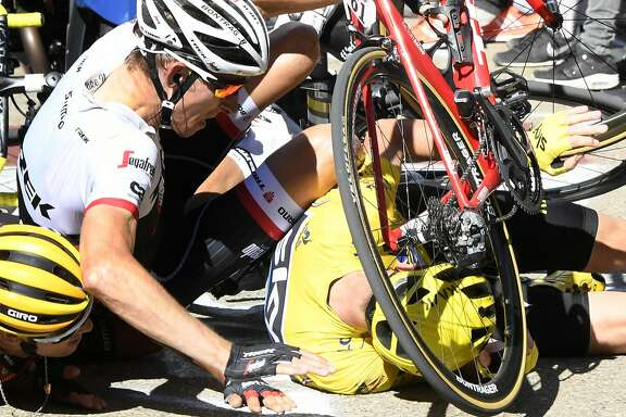 """Britain's Chris Froome, wearing the overall leader's yellow jersey, right, Netherlands� Bauke Mollema, center, and  Australia�s Richie Porte crash at the end of the twelfth stage of the Tour de France cycling race with start in Montpellier and finish six kilometers (3.7 miles) before the Mont Ventoux, France, Thursday, July 14, 2016. The wind, combined with a temperature just above the freezing level on top of the """"Giant of Provence,"""" forced organizers to move the finish line six kilometers (3.7 miles) down the road to the Chalet Reynard. (Bernard Papon/ Pool Photo via AP)"""