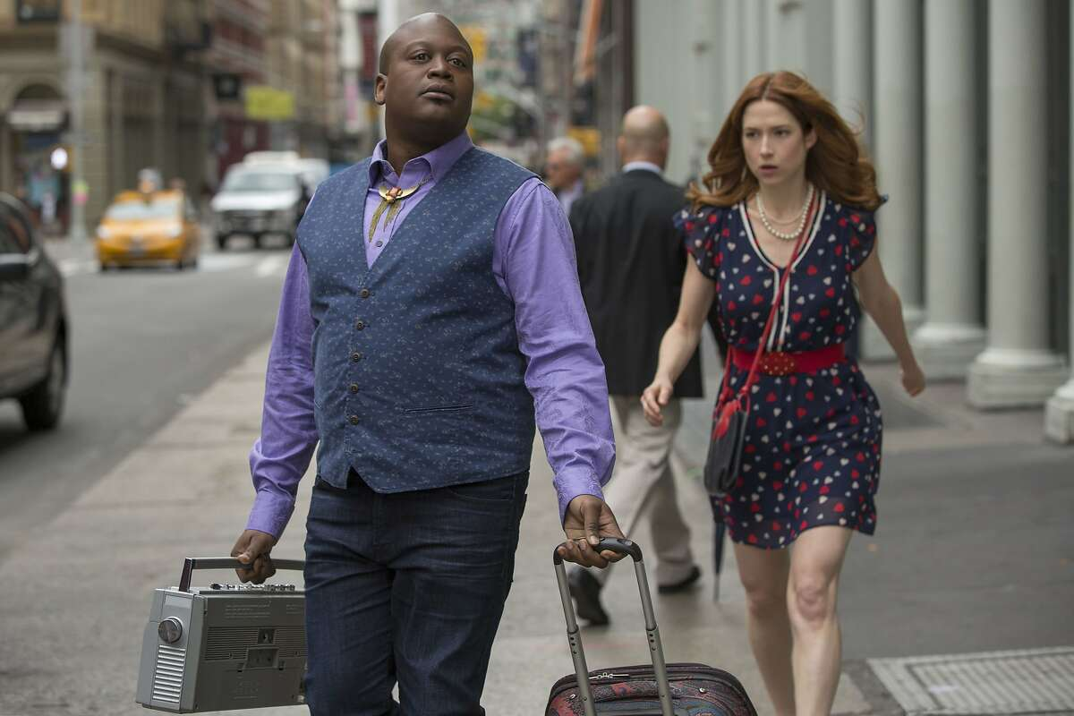 In this image released by Netflix, Tituss Burgess, left, and Ellie Kemper appear in a scene from