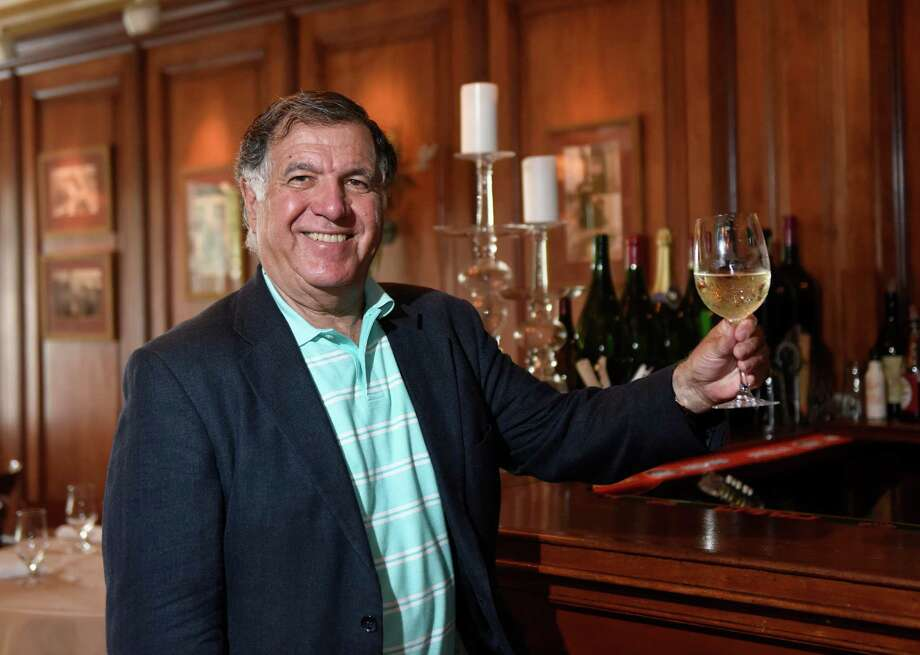 Greenwich Wine Society Director Dean Gamanos holds a glass of Pino Grigio, one of his favorite types of wine, at The Ginger Man in Greenwich, Conn. Thursday, July 14, 2016. The Greenwich Wine Society was founded in 2008 and meets up frequently for wine tastings, dinners and bus trips to local vineyards. The club is an informal meetup for wine enthusiants to meet, network and make new friends. Photo: Tyler Sizemore / Hearst Connecticut Media / Greenwich Time