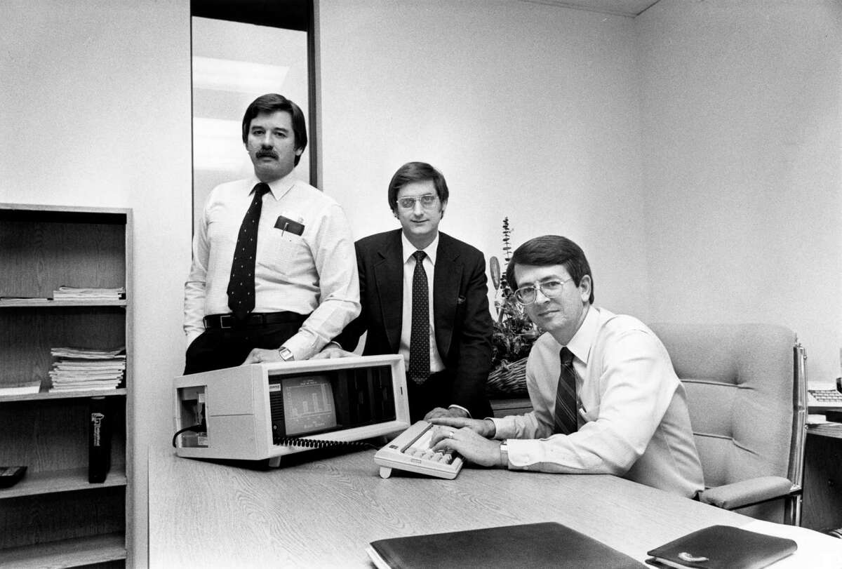 Compaq founders Jim Harris, from left, Bill Murto and Rod Canion pose in 1982 with their IBM-compatible portable computer.