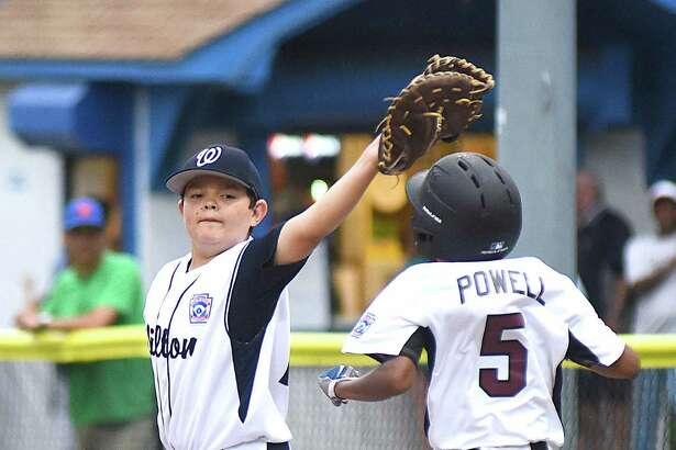 Wilton first baseman Alex Reyes, left, holds the bag with the ball in his glove at Stamford National runner Zach Powell hits first base during last week's District 1 11-year-old championship game.