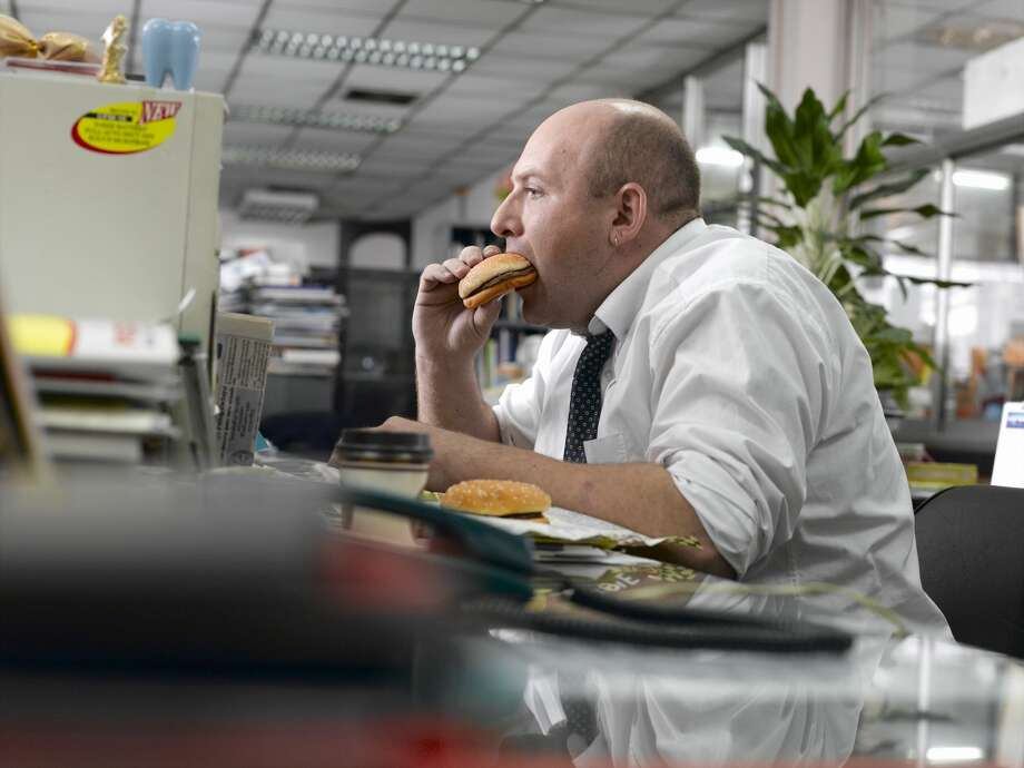 al desko: eating at one's desk in an office. Photo: Hummer/Getty Images