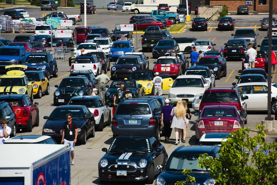 Mini Coopers fill the Midland Plaza parking lot, punctuated by other types of cars as visitors come to view the Minis during the biennial Mini Takes the States rally stop in Midland on Thursday. Mini Cooper drivers are traveling cross-country raising funds and awareness for the charity Feeding America. Photo: Danielle McGrew Tenbusch