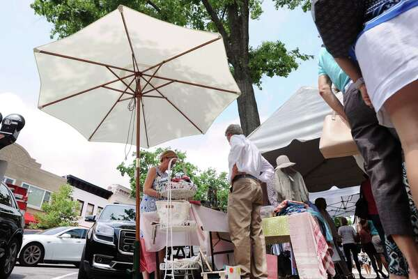 Anne Tabacco of Beach Box at Out of the Box store, made use of a patio umbrella to shade customers from the sun during the annual Sidewalk Sales organized by the Greenwich Chamber of Commerce on Greenwich Avenue, Greenwich, Conn., Thursday, July 14, 2016. According to the Greenwich Chamber of Commerce website, over 120 businesses are participating in the central Greenwich sales event that features merchants offering deep discounts on brand items under small tents placed outside their stores. The event runs from 10 a.m. to 6 p.m. on Friday and Saturday, and from 11 a.m. to 5 p.m. on Sunday, the final day of the sales.