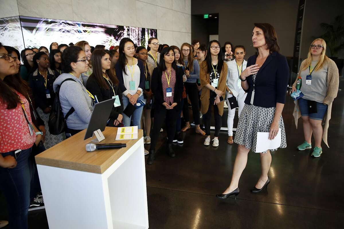 Joan Scott (right), director of community relations at Dolby Laboratories, welcomes high schoolers to a Girls Who Code event at the Dolby Laboratories headquarters in San Francisco, California, on Thursday, July 14, 2016.