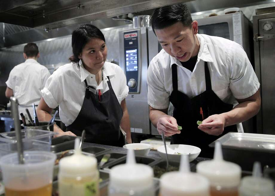 Brandon Chang (right), a line cook at Mr. Jiu's, chats with Kim Hirota as he helps prepare dinner at the new Chinatown restaurant, the first he has worked at that provides health insurance for employees. Photo: Carlos Avila Gonzalez, The Chronicle