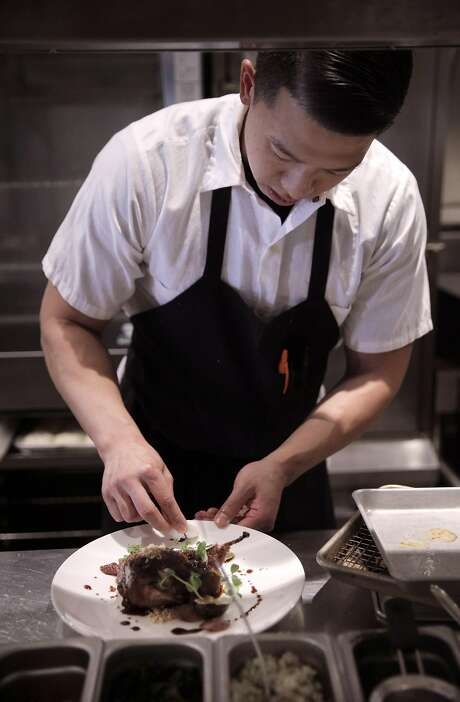 Line cook Brandon Chang preps a quail stuffed with sticky rice, sausage and figs at Mister Jiu's. Photo: Carlos Avila Gonzalez, The Chronicle