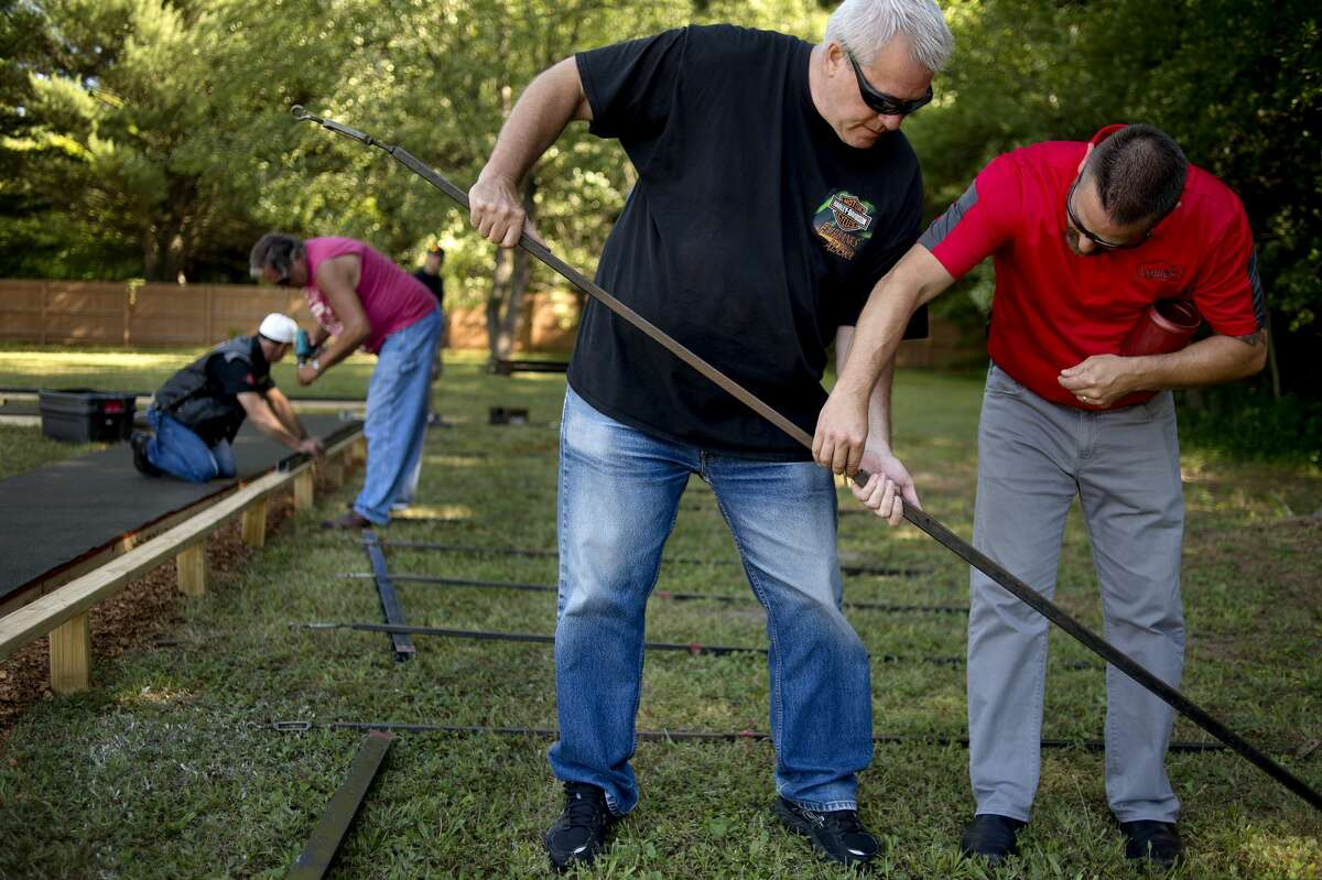 From left: Terry Wower of Sanford and Martin Brennan of Midland attach railing for 140 name panels to be placed in while Eddie Bishop of Midland and Chad Hopkins of Sanford assemble frames for The Moving Wall, a traveling half-size replica of the Vietnam Veterans Memorial, at the American Legion in Sanford on Thursday morning. The wall will be in Sanford until Monday when it will be disassembled to travel to Palmerton, PA.