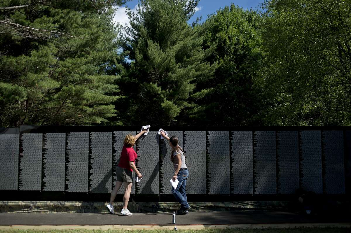 Midland residents Dee Stone, left, and Susan Bland wipes down panels of the, The Moving Wall, a traveling half-size replica of the Vietnam Veterans Memorial, at the American Legion in Sanford on Thursday morning.