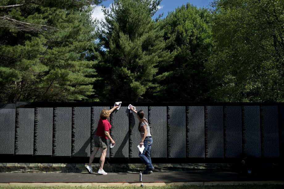 Midland residents Dee Stone, left, and Susan Bland wipes down panels of the, The Moving Wall, a traveling half-size replica of the Vietnam Veterans Memorial, at the American Legion in Sanford on Thursday morning. Photo: Brittney Lohmiller/Midland Daily News/Brittney Lohmiller