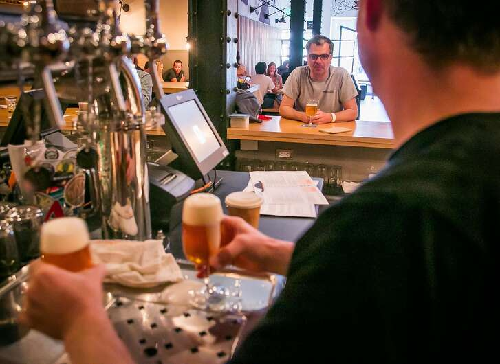 Bartender Rich Allen talks with a customer at Mikkeller in San Francisco, Calif., on Saturday, May 24th, 2014.