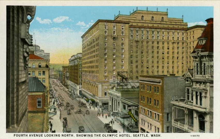 !920s: Vintage postcard showing the view looking up Fourth Avenue showing the Olympic Hotel. Other multi-story buildings are visible and traffic fills the street.