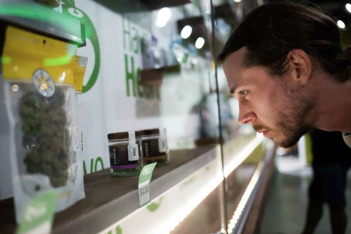 Matt Schnitzel looks at various packages of recreational marijuana at Have a Heart's newest store in Belltown, on Tuesday, July 12, 2016.