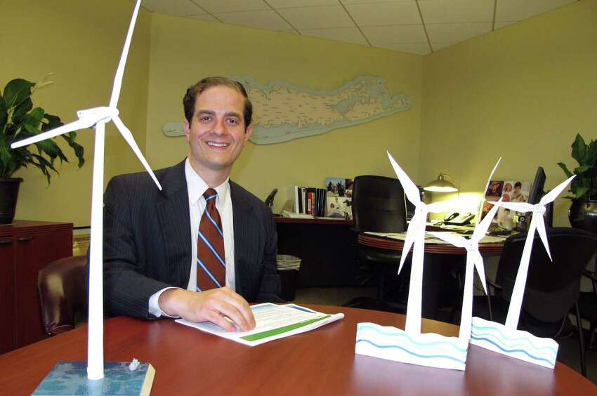 In this July 13, 2016 photo, Long Island Power Authority Chief Executive Officer Thomas Falcone sits in front of some models of offshore wind turbines at the utility's offices in Uniondale, N.Y. Falcone tells The Associated Press the utility is moving forward with plans to construct the nation's largest wind energy farm off eastern Long Island. (AP Photo/Frank Eltman) ORG XMIT: RPFE101