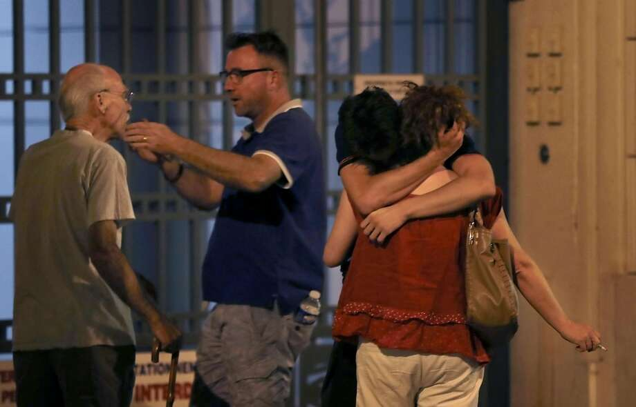 "People react in the French Riviera town of Nice after a truck drives into a holiday crowd watching a fireworks display on Bastille Day. The incident that killed dozens of people is being called an ""attack."" Photo: VALERY HACHE, AFP/Getty Images"