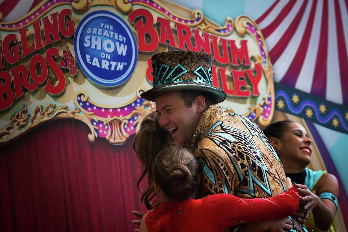 Ringling Bros. and Barnum & Bailey Circus Xtreme ringmaster David Shipman embraces other circus performers after giving a performance to children at MD Anderson Children's Cancer Hospital, Thursday, July 14, 2016, in Houston.