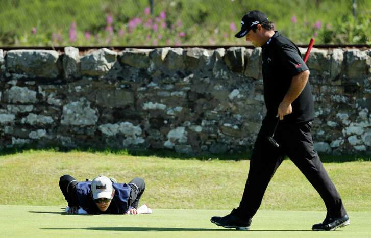 Patrick Reed's caddie Kessler Karain gets a useful perspective as he helps line up a putt on the 11th green at Royal Troon Golf Club. Reed used whatever advice Karain gleaned from his pushups to shoot a 63.