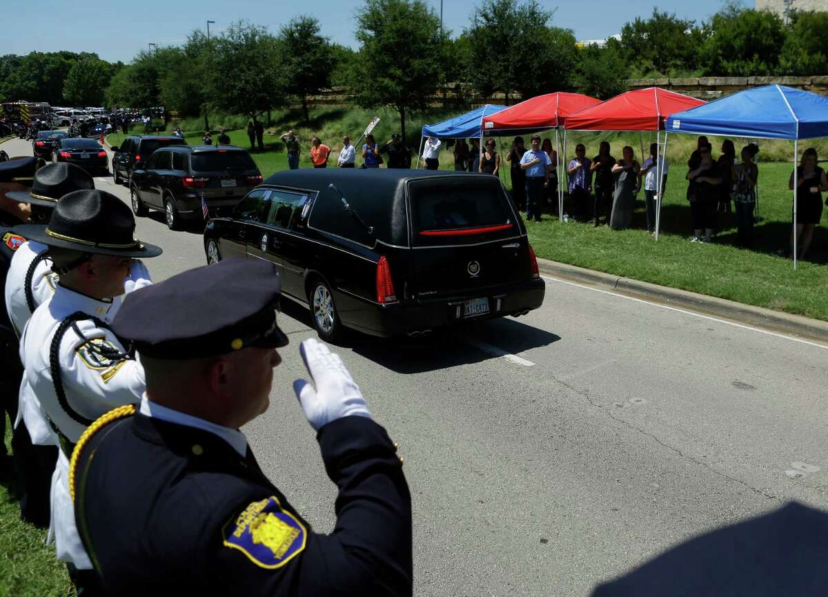 Officers salute as the hearse carrying Dallas police Sergeant Michael Smith drives by following his funeral at Watermark Community Church, Thursday, July 14, 2016, in Dallas.