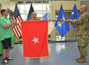 New York Army National Guard Brig. Gen. Patrick Center, center, stands at attention as Warrant Officer Matt Starr and his brother Joe Center unroll his general officers flag during a promotion ceremony in Latham.