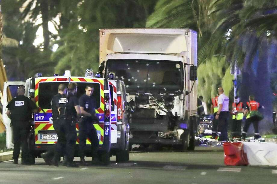 Police officers and rescued workers stand near a van that ploughed into a crowd leaving a fireworks display in the French Riviera town of Nice on July 14, 2016. The mayor of the French city of Nice said dozens of people were likely killed after a van rammed into a crowd marking Bastille Day in the French Riviera resort today and urged residents to stay indoors.  / AFP PHOTO / VALERY HACHEVALERY HACHE/AFP/Getty Images Photo: VALERY HACHE, Staff / AFP/Getty Images / AFP or licensors