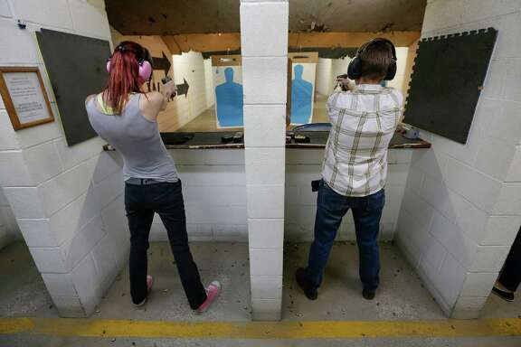 Krysta McClaskey, left, and her wife, Melissa, discharge their weapons during a license-to-carry class at a Houston gun range.