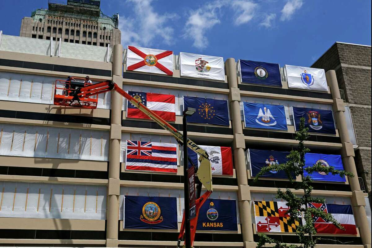 Workers hang state flags on the side of a parking garage next to the Quicken Loans Arena in downtown Cleveland, Ohio, Thursday, July 14, 2016, in preparation for the upcoming Republican National Convention. (AP Photo/Gene J. Puskar)